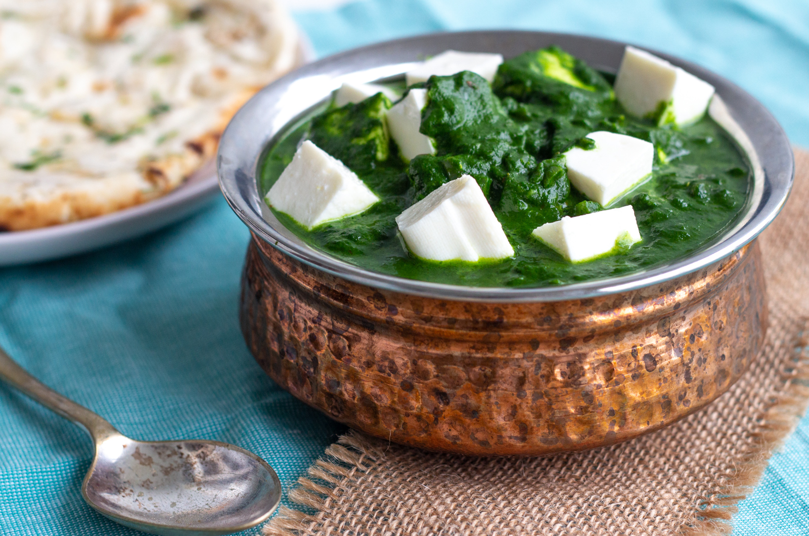 A copper coloured serving bowl is filled with palak paneer or spinach curry with Indian cottage cheese cubes in it. To the left of the palak paneer is a piece of naan, and at the bottom of the image a silver coloured spoon can be seen peeking.