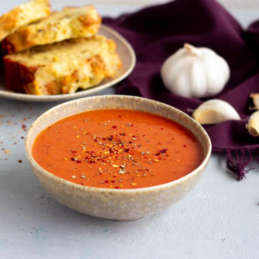 A bowl of roasted tomato garlic soup in the front. On the back of the soup is a plate with three slices of cheese bread, and a garlic bulb, along with a few cloves of garlic on a purple napkin.