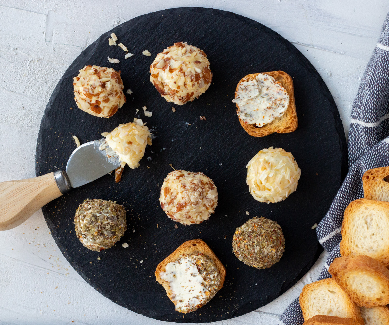 Assorted mini cheese balls set on a black slate platter. There are a 6 mini cheese balls coated with herbs, almonds and onion flakes. There are also mini toasts with cream cheese spread on them along with a cheese knife.