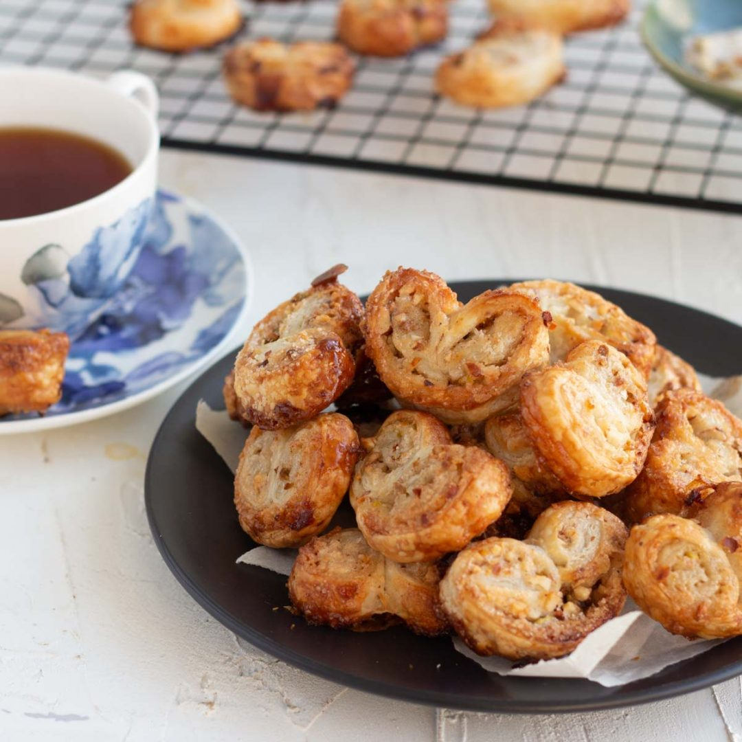 A black plate with a stack of cinnamon nut puff pastry palmiers in the front. At the back is a baking tray with more palmiers, and on the left is a cup of black tea with a palmier on the saucer.
