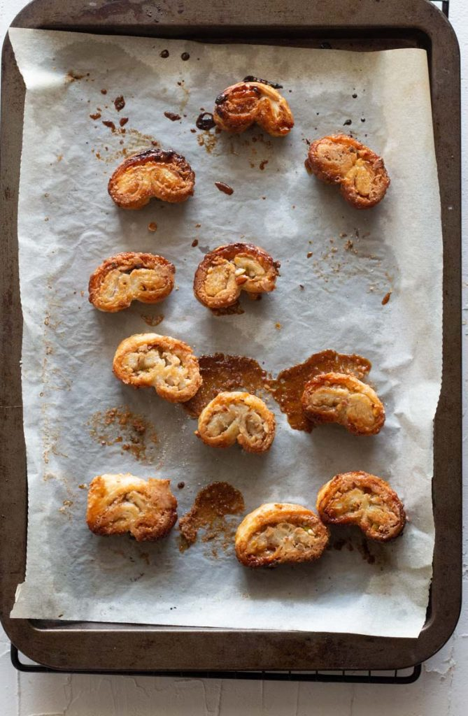 A top down shot of a baking tray lined with parchment on which are puff pastry palmiers.
