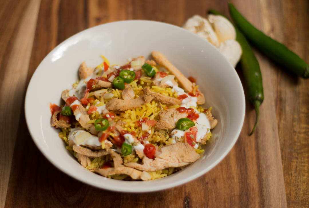 Halal cart style chicken and rice is an iconic New York street food comprising of shawarma style sliced chicken piled on top of spiced yellow rice served with salad and pita bread. This is then drizzled with a tangy white sauce and a spicy hot sauce.