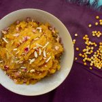 Picture of chana daal halwa or Chanay ki Daal Halwa. A traditional Pakistani / Indian dessert. It shows a white bowl on a purple background with bengal gram spread around the bowl.