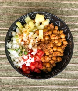 A bowl of boiled chickpeas with diced and boiled potatoes, diced onions, diced tomatoes and green chilies