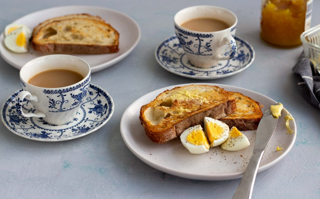 A breakfast setting with two cups of tea, along with a plate that has two slices of toast, three pieces of boiled eggs and a butter knife.