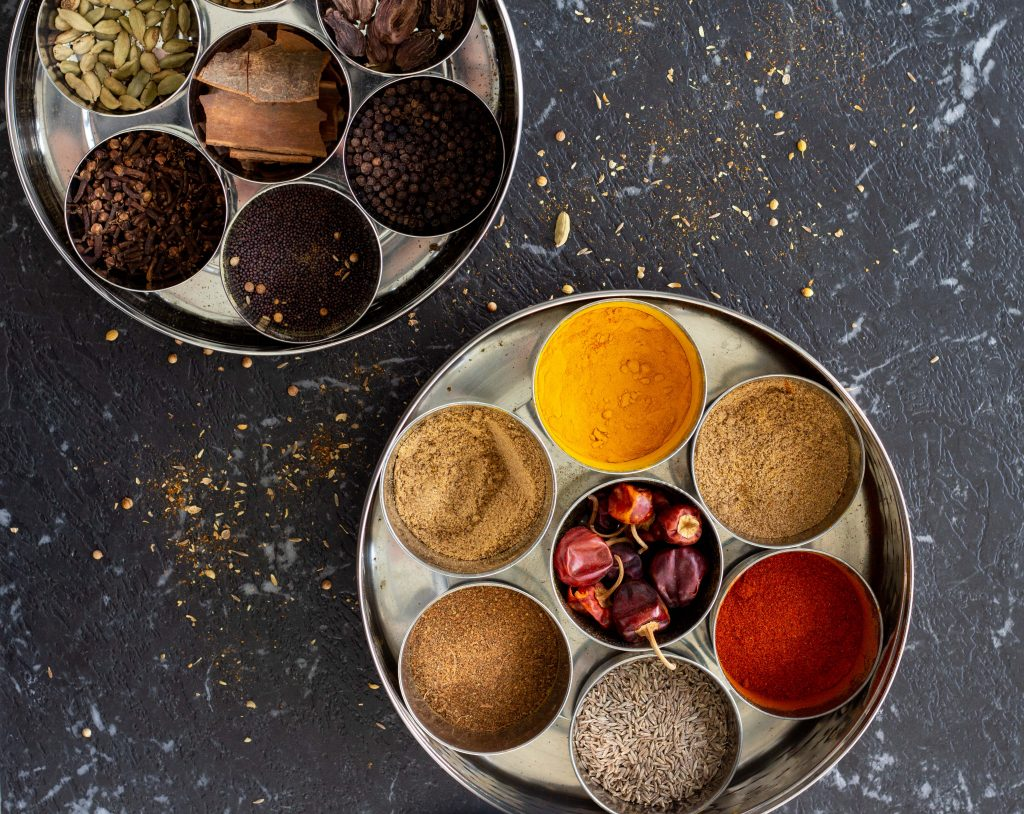 Two Indian masala dabbas (spice boxes) on a black background.
