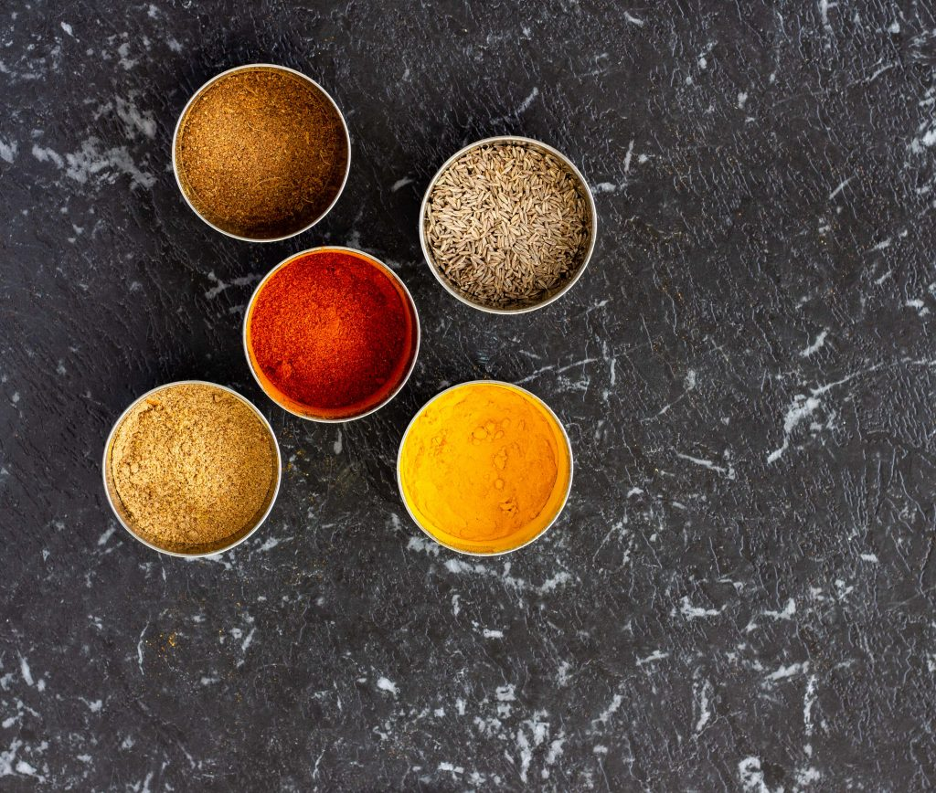 Spices that are regularly used in a Desi kitchen placed in small steel bowls- they include red chilli powder, coriander powder, turmeric, cumin seeds and garam masala.