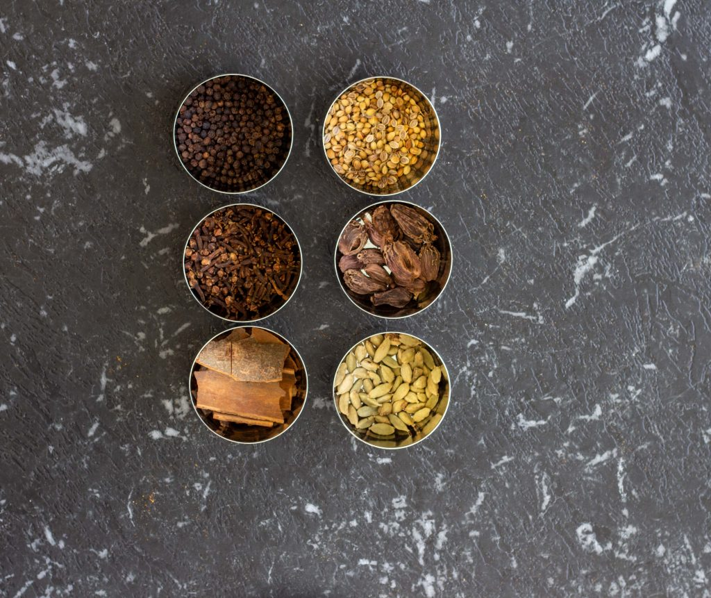 Whole spices that are used regularly in a Desi kitchen placed in small steel bowls - they include cinnamon sticks, cloves, cardamom, black peppercorn, black cardamom and fenugreek seeds.