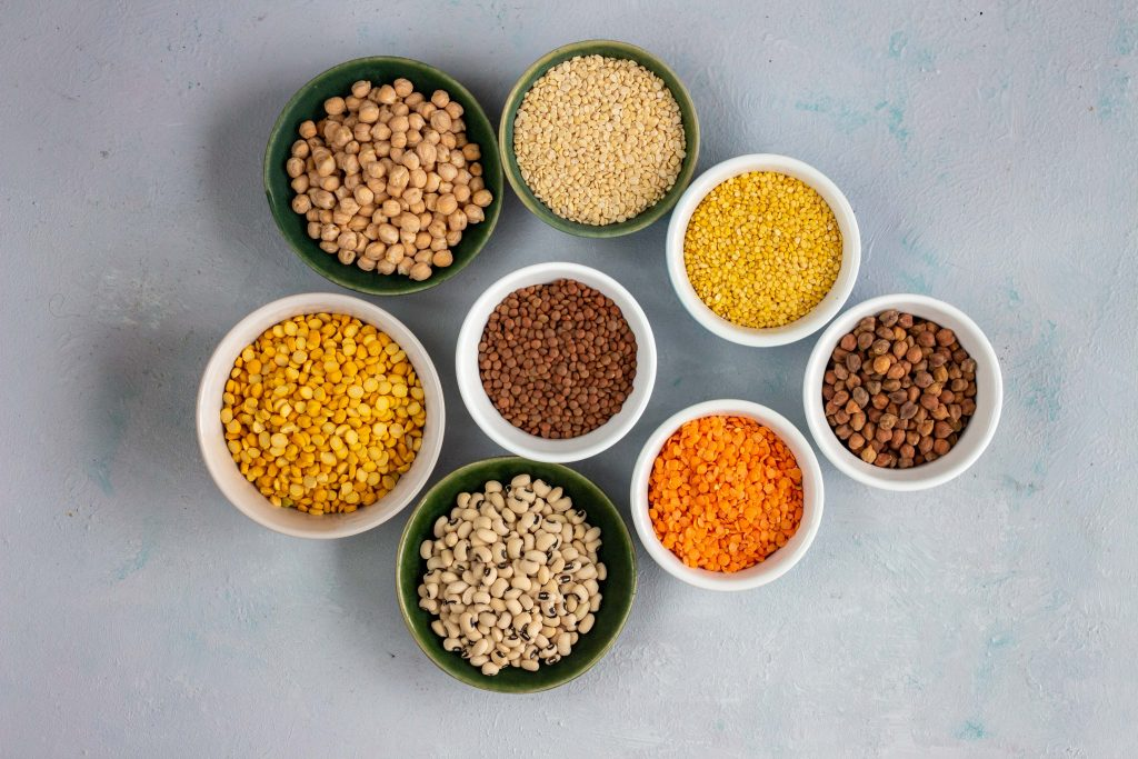 8 types of Pakistani lentils in different bowls of varying sizes.