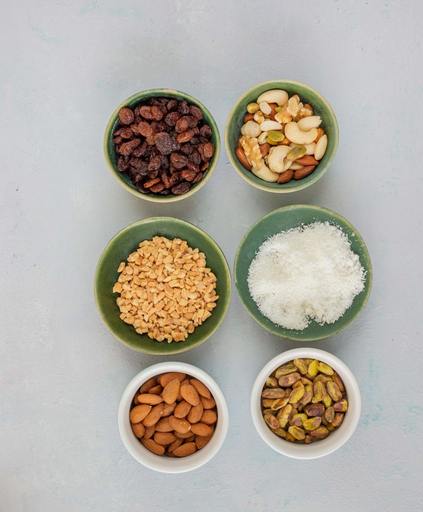 Different types of nuts used in a Desi Pakistani kitchen. Items include raisins, pistachios, almonds, peanuts and coconut.