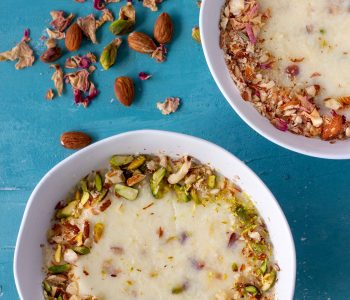 Two bowls of chawal ki kheer (Pakistani rice pudding). The bowl on the bottom left is garnished with crushed almonds and sliced pistachios. Above that, on the right corner is another bowl of the rice pudding, this one decorated with crushed almonds and dried rose petals. Next to the bowl on the left are scattered almonds, pistachios and dried rose petals.