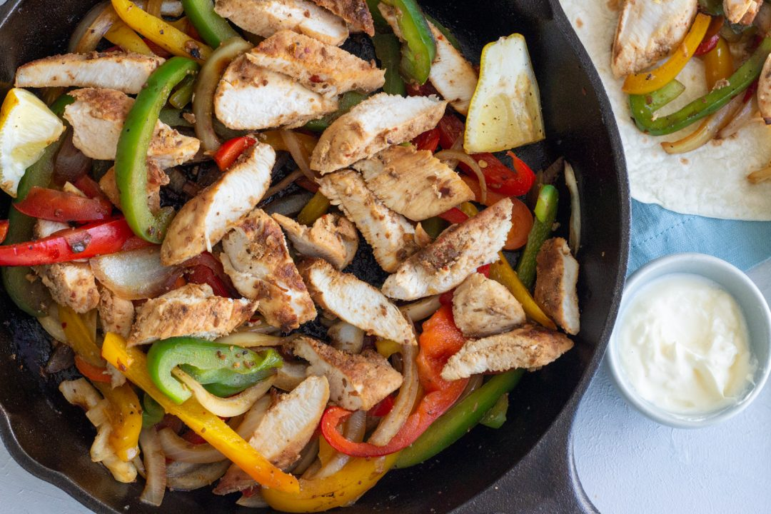 A cast iron skillet with easy chicken fajitas - red, yellow and green bell peppers and onions. Next to the skillet is a small blue bowl with sour cream, and on top is a tortilla peeking through with some of the fajita filling in it.