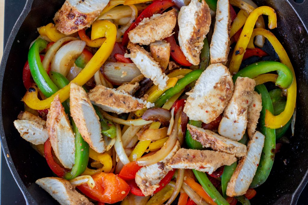 A cast iron skillet with easy chicken fajitas - red, yellow and green bell peppers and onions.