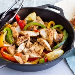 A cast iron skillet with chicken fajitas, red, yellow and green bell peppers and onions. Next to the skillet is a small blue bowl with sour cream, and on top is a tortilla peeking through with some of the fajita filling in it.