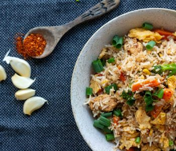 A white bowl filled with chilli garlic fried rice with eggs, vegetable and sliced chicken, and topped with spring onions. On the top left of the bowl is a small wooden spoon with red chilli flakes spilled around it. Below the wooden spoon are 4 cloves of garlic.