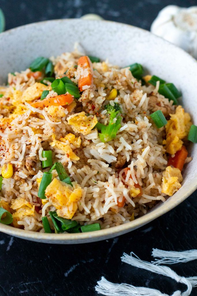 A white bowl filled with chilli garlic fried rice with eggs, vegetable and sliced chicken, and topped with spring onions.
