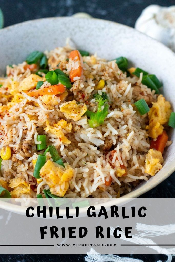 """A white bowl filled with chilli garlic fried rice with eggs, vegetable and sliced chicken, and topped with spring onions. Below the bowl is text that states """"chilli garlic fried rice"""" along with the website name - www.mirchitales.com"""