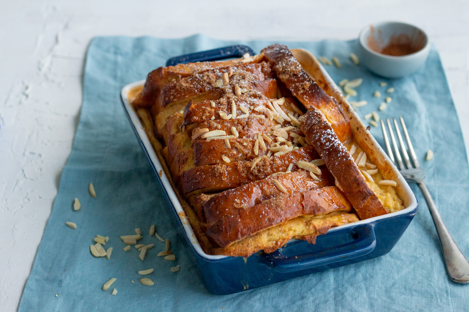 An overnight french toast bake made using brioche bread is placed in a dark blue tray with sliced almonds top. The tray is kept on a blue napkin, and there is a fork on the right with a small blue bowl of cinnamon at the back.