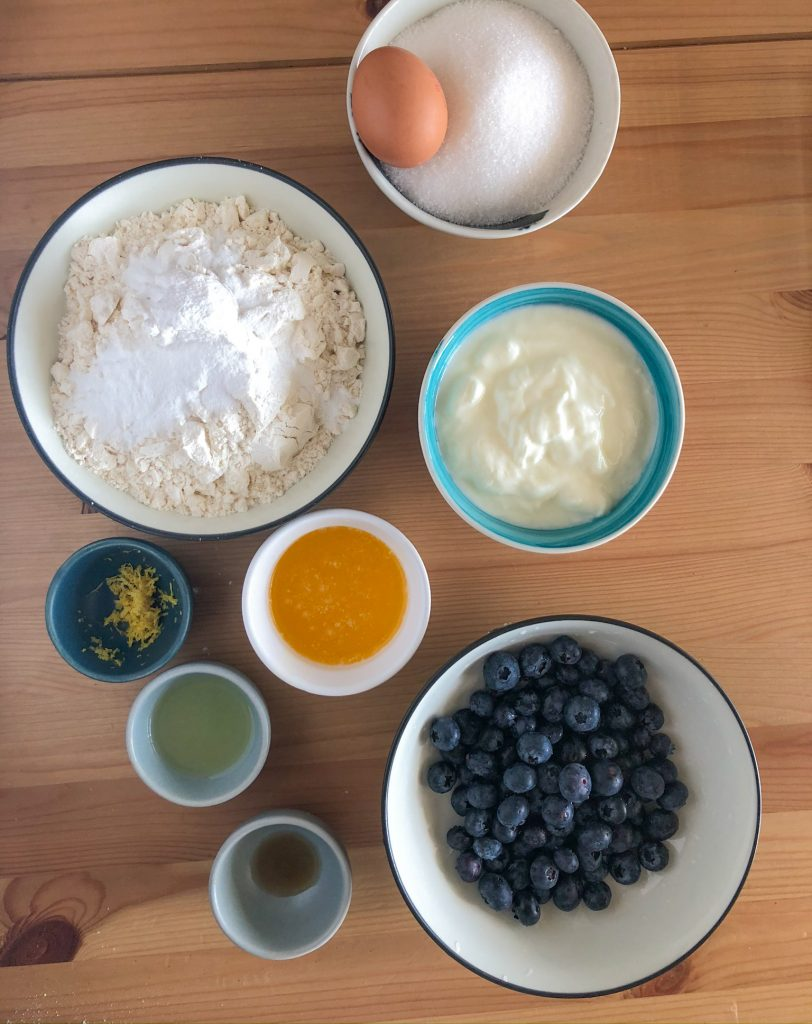 Ingredients for lemon blueberry muffins set out. Clockwise from the top is a bowl of sugar with an egg in it, then yoghurt, blueberries, vanilla essence, lemon juice, lemon zest, melted butter and flour with baking soda and salt.