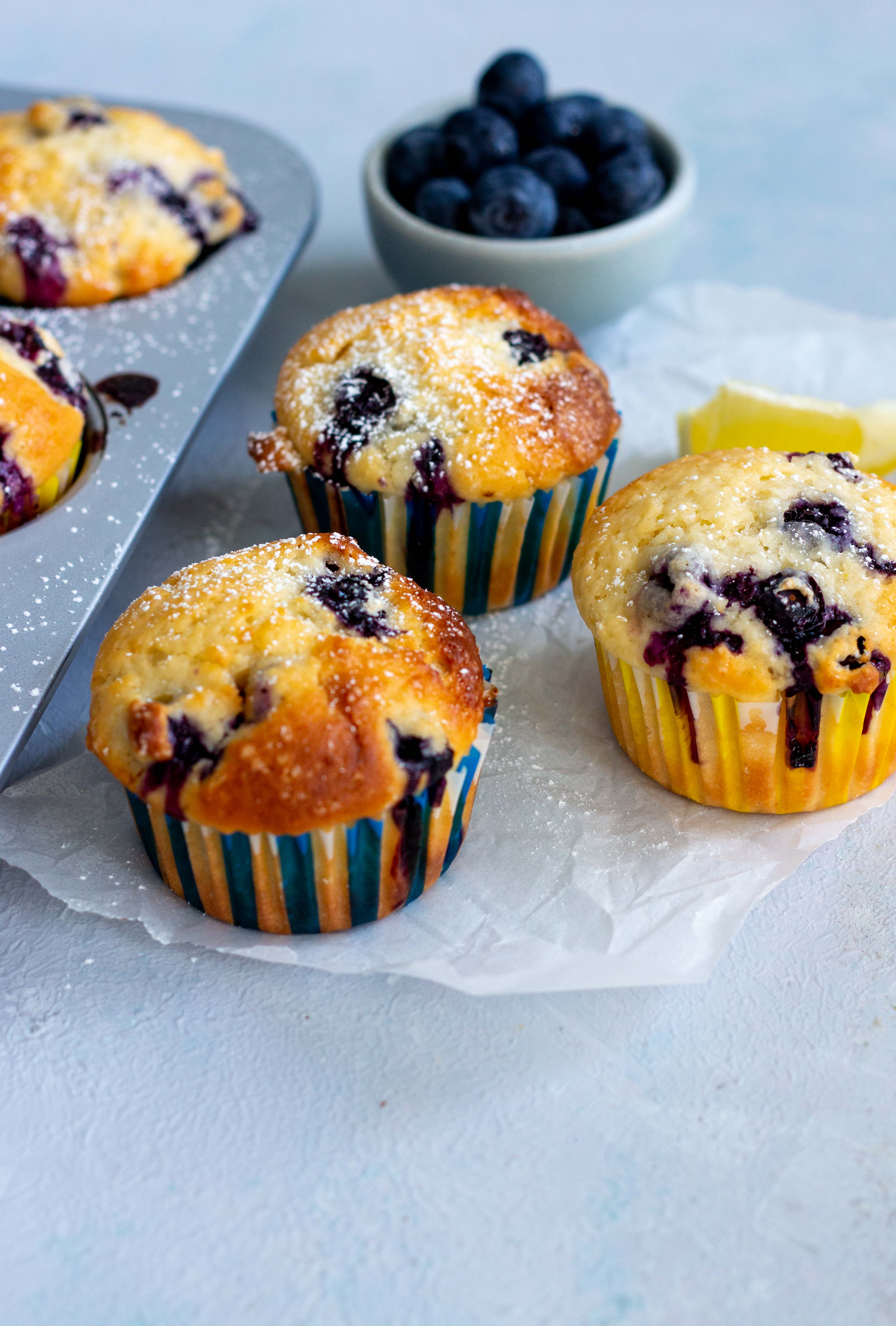 A muffin tray peeking from the left hand sided with two lemon blueberry muffins in it. Next to the tray are three lemon blueberry muffins on top of parchment paper. A mini light blue bowl with blueberries is at the back of the muffins.