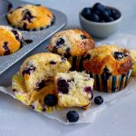 A muffin tray peeking from the left hand sided with two lemon blueberry muffins in it. Next to the tray are three lemon blueberry muffins, with the one in front half torn apart. A mini light blue bowl with blueberries is at the back of the muffins.