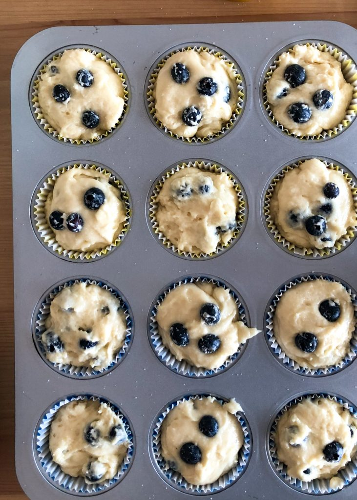 A 12 cup muffin tray with raw lemon blueberry muffin batter in it.