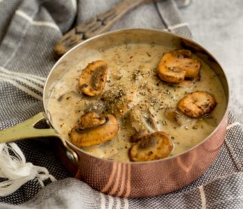 A copper coloured saucepan filled with mushroom sauce topped with five golden brown mushrooms, salt and black pepper. This copper saucepan is placed on top of a black and white striped napkin and on the top of image, the edge of a wooden spoon is peeking through.