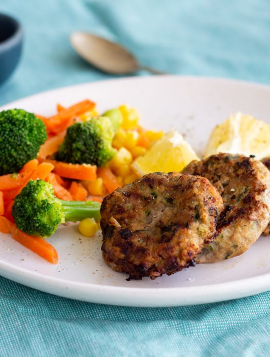 A white plate with three turkey rissoles on it with three lemon wedges and steamed carrots, broccoli and corn. Behind the plate is a mini bowl of ketchup and a small golden spoon.