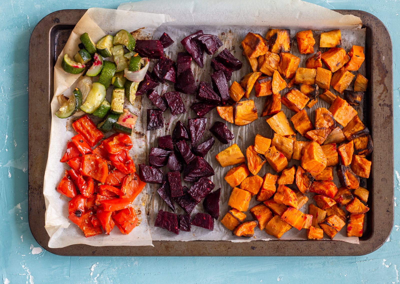 A baking tray with roasted vegetables on it cut in cubes - the vegetables are sweet potato, beetroot, red capsicum / red bell pepper and zucchini.