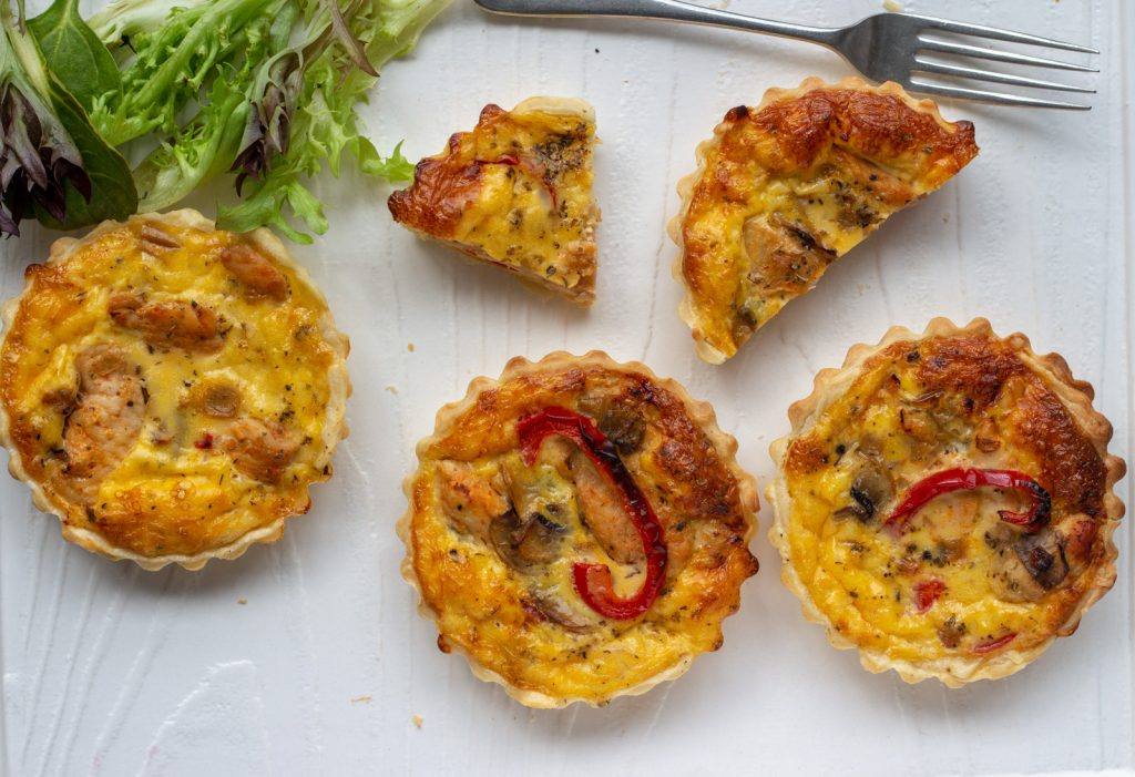 Four chicken and mushroom mini quiches with roasted capsicum on a white platter. One of the mini quiches is cut in half, and a quarter. There is also a small salad at the back.