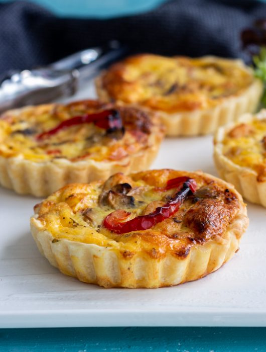 Four chicken and mushroom mini quiches with roasted capsicum on a white platter. There's a silver tong in the background.