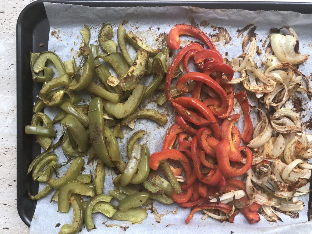 A tray of roasted vegetables - on the left end is roasted green capsicum or green bell pepper, and in the middle are roasted red capsicum. or red bell pepper. On the right are roasted and sliced onions.