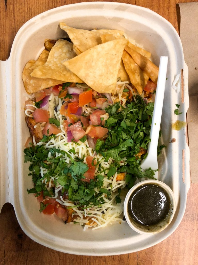 A takeaway box with tortilla chips, salsa, coriander leaves, cheese and green chili sauce.