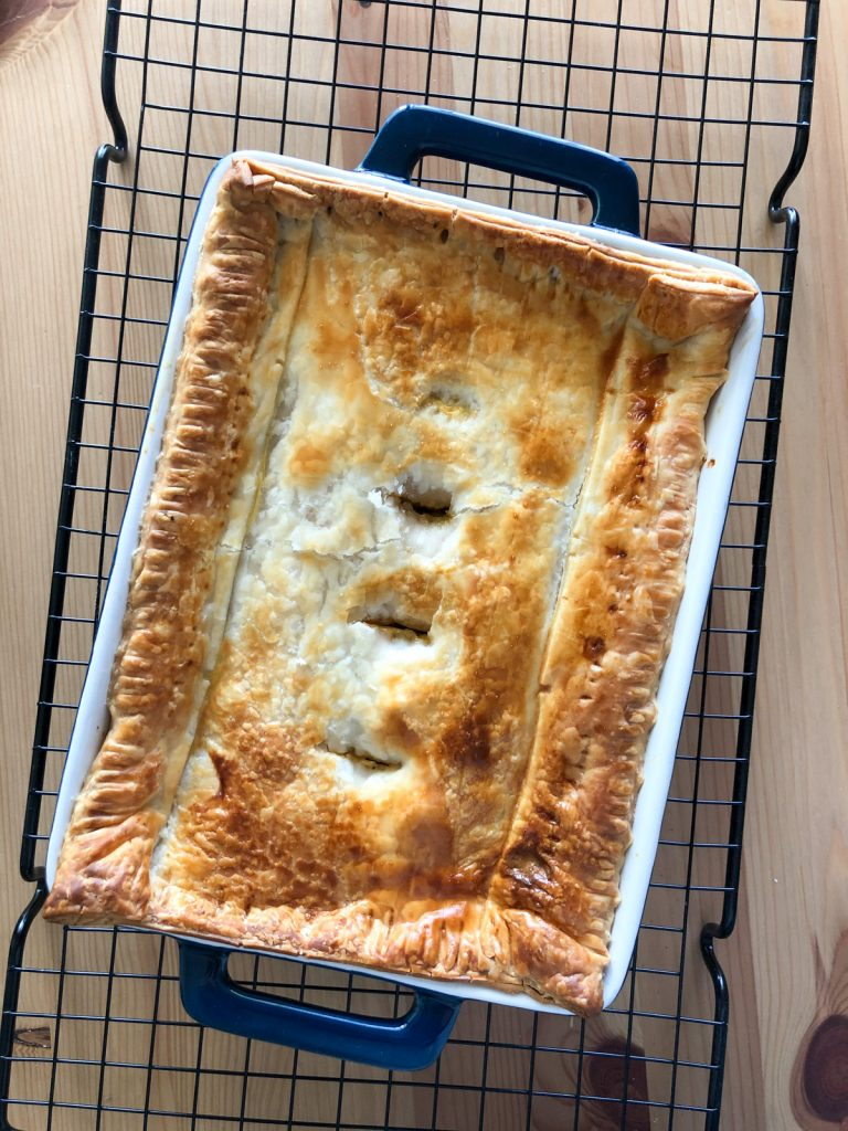 A chicken pot pie with puff pastry on top is made in a rectangle dark blue ceramic glass tray. The tray is kept on a wire rack.