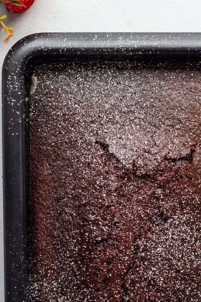 A quarter of a one bowl chocolate cake in a rectangle baking tray.