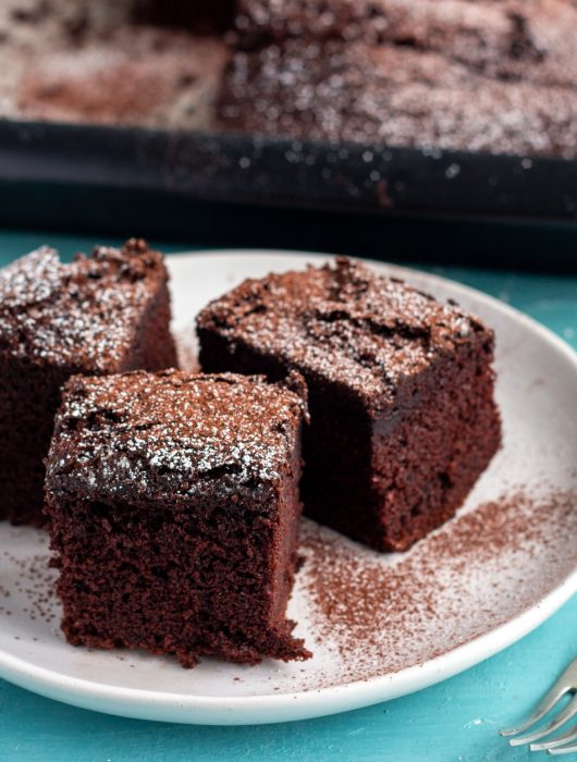 Three slices of one bowl chocolate cake on a white plate, and dusted with icing sugar and cocoa powder. On the back of the plate is a tray with chocolate cake in it.