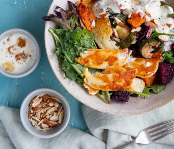 A bowl of roast vegetable salad with halloumi salad. Next to the bowl is a fork, a small bowl of crushed almonds, and a bowl of garlic yoghurt dressing.
