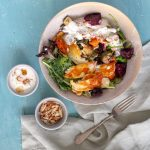 A bowl of roast vegetable with halloumi salad. Next to the bowl is a fork, a small bowl of crushed almonds, and a bowl of garlic yoghurt dressing.