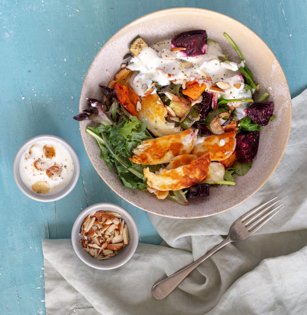 A bowl of roast vegetable salad with halloumi. Next to the bowl is a fork, a small bowl of crushed almonds, and a bowl of garlic yoghurt dressing.