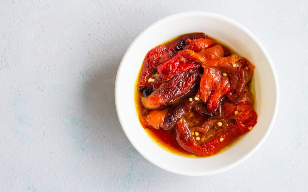A bowl of roasted red peppers with oil.