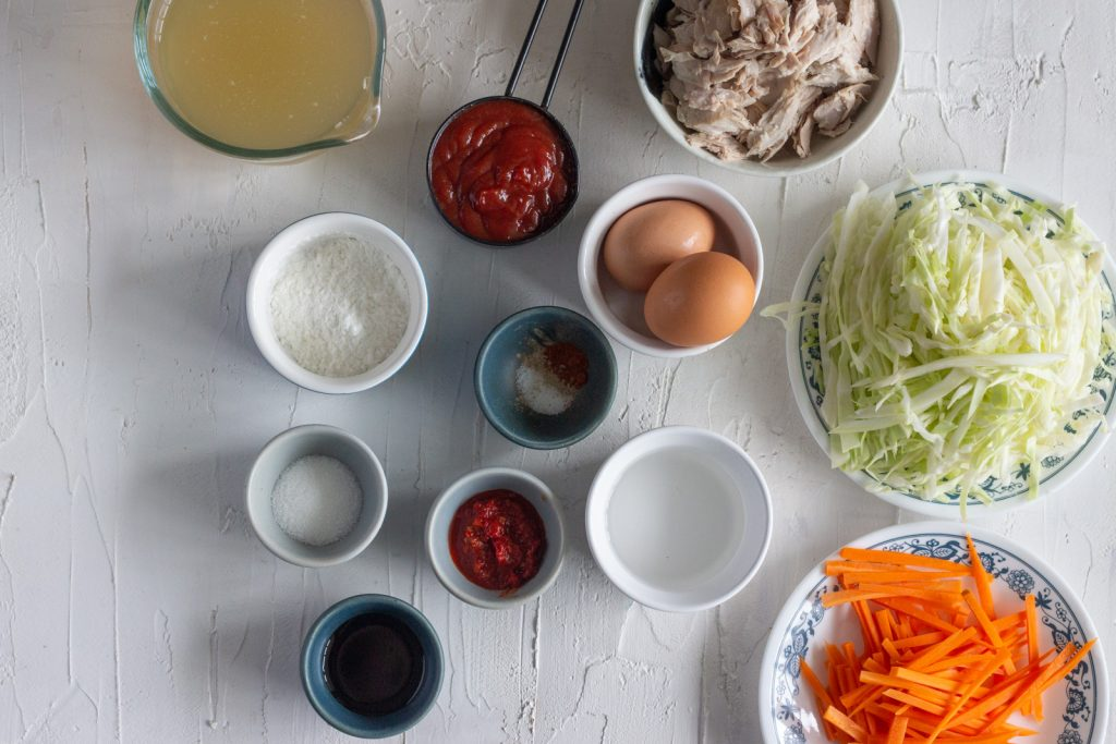 Ingredients laid out for chicken hot and sour soup. The ingredients are from top left - chicken stock, boiled chicken, cabbage, carrots, soy sauce, salt, cornflour, tomato ketchup, eggs, vinegar, salt and white pepper, and red chili paste.
