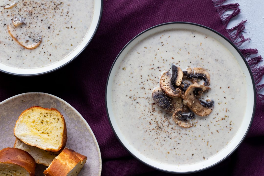 A bowl of creamy mushroom soup with another bowl at the back, along with garlic bread.