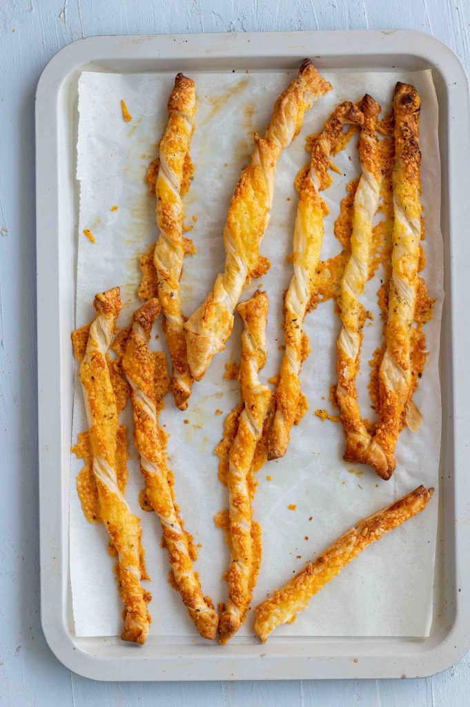 Puff pastry cheese straws right out of the oven placed on a baking tray.