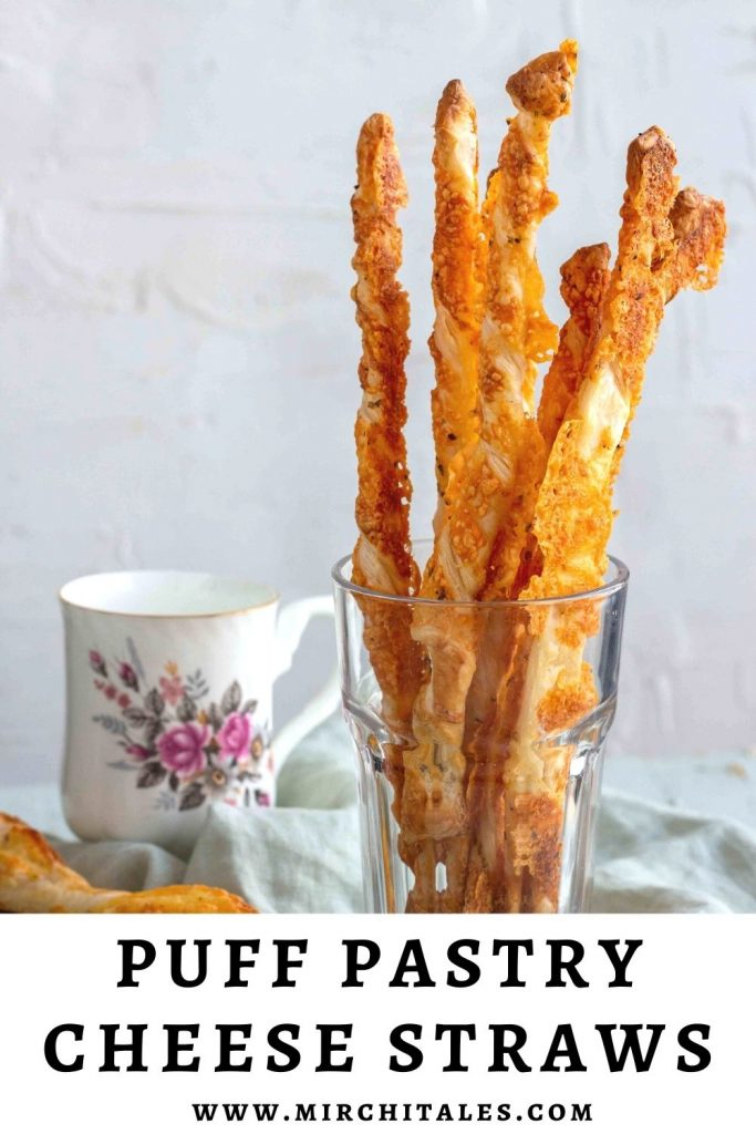 A couple of puff pastry cheese straws in a clear glass with a tea mug in the background.