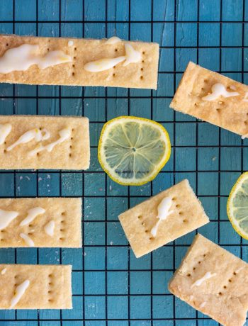 7 lemon and cardamom shortbread cookies on a baking tray, with slices of lemon around the cookies. On top of the shortbread cookies is a lemon glaze.