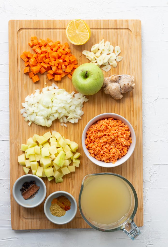Ingredients laid out for vegetarian mulligatawny soup on a wooden chopping board. Ingredients are carrots, onions, potatoes, spices, whole spices, vegetable stock, lentils, apple, ginger, garlic and lemon.