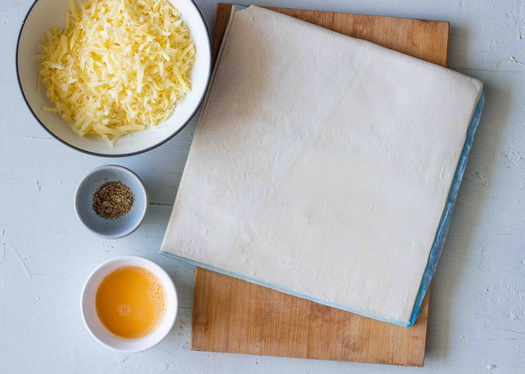 Ingredients laid out for puff pastry cheese straws. The ingredients are puff pastry, grated cheddar cheese, dried mix Italian herbs and an egg.