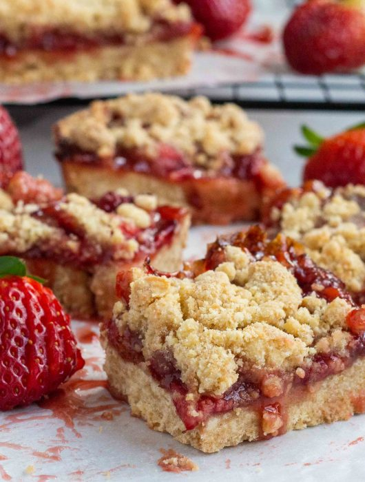 A picture of strawberry jam bars with fresh strawberries. There are 4 pieces cut into bars, and the rest is uncut.