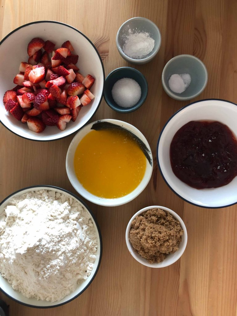 Ingredients laid out for strawberry jam bars. Ingredients are flour, brown sugar, melted butter, strawberry jam, baking soda, salt, cornflour and chopped strawberries.