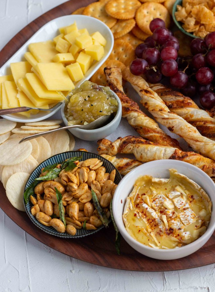 How to make a Cheese Board or South Asians - from bottom left there is Baked Brie, masala peanuts, rice crackers, grilled and cubed cheese, puff pastry straws, mango chutney, and grapes.